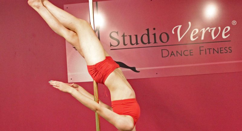 Michaela holding an advanced pole dance skill called a Crossed Leg Layback