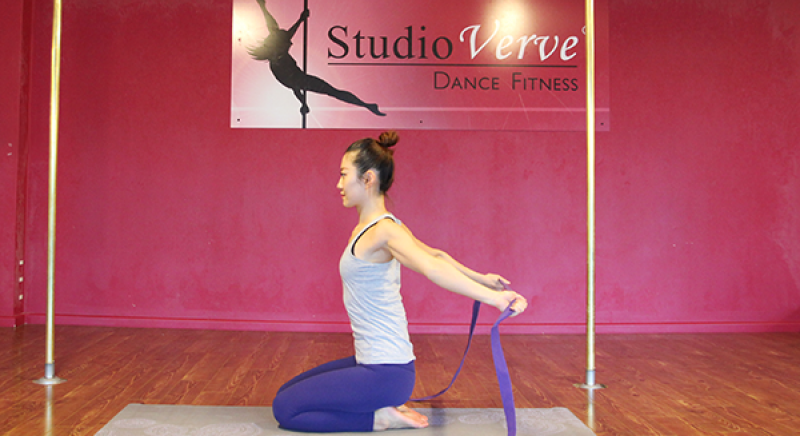 Student Nadine demonstrates a shoulder opening exercise