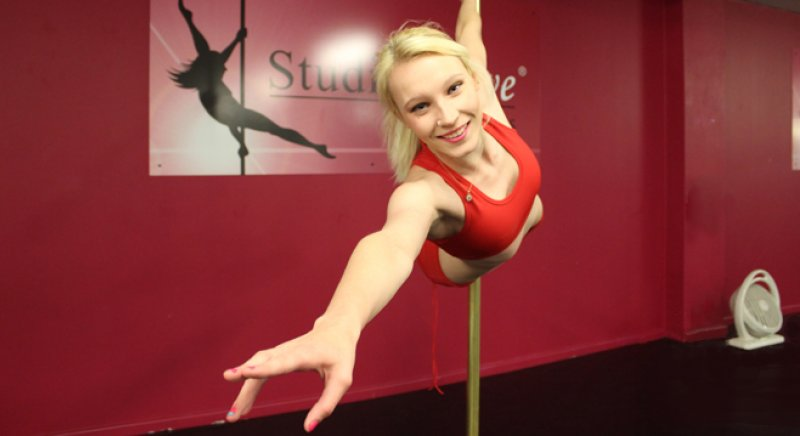 Advanced pole dancing student Michaela holding a Superman leg hold on the pole