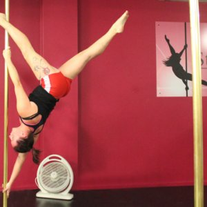 "PoleFit student Chelsea Booth demonstates an Advanced Pole Dance skill called ""Extended Butterfly"""